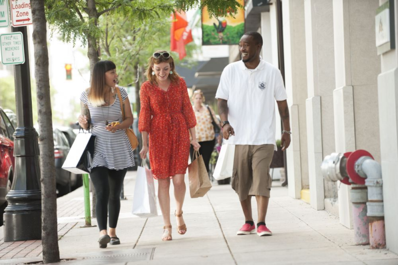 Three young adults walking down city sidewalk carrying shopping bags.